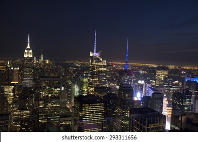 Manhattan Skyline and Empire State Building, viewed from Rockefeller Plaza at night, New York City.
