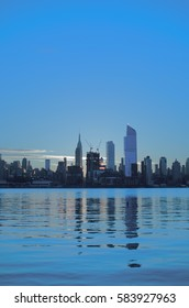 The Manhattan skyline reflects in the Hudson River as the sun rises over the city