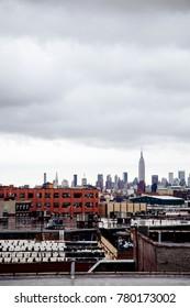 The Manhattan skyline as seen from a Brooklyn rooftop onan inclement day.