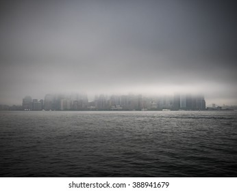 manhattan skyline seen from the harbor during foggy, gray weather