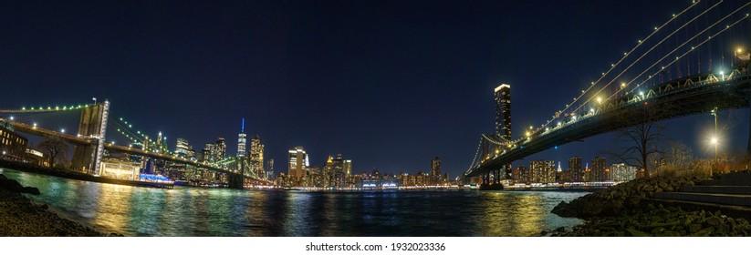 Manhattan skyscrapers between Brooklyn Bridge and Manhattan bridge, Golden night light view from Brooklyn, New York, United States. 03.07.2021