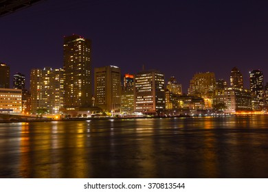 Manhattan skyscrapers with colorful reflections in East River at night. A view on Manhattan from Roosevelt Island at night in New York, USA.