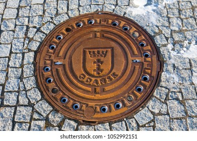 Manhole cover with Gdansk emblem. Gdansk, Pomerania, Poland.