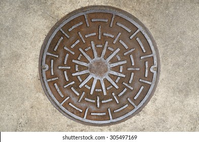 Manhole cover on street, top view.