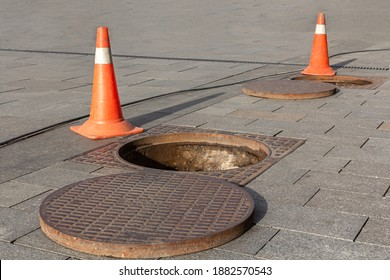 Manhole cover open in street and repair of roads. Accident with sewer hatch in city. Concept of sewage, underground utilities.