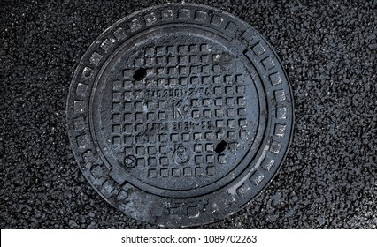 manhole cover in the road of asphalt