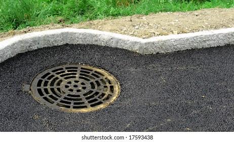 Manhole next to a border
