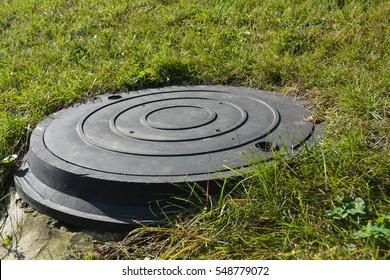 Manhole plastic cover in the garden lawn
