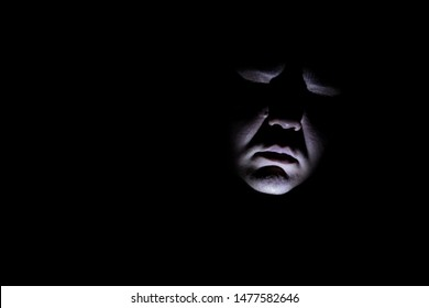 Maniac face silhouette illuminated by torch on black background. Dark background. Horror background. Black background. Halloween horror concept.