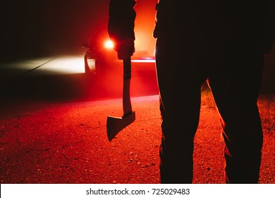 maniac killer near the car at night close-up. silhouette of a man with an ax in his hand at night in a fog