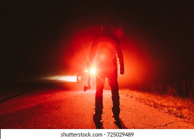 maniac killer near the car at night. silhouette of a man with an ax in his hand at night in a fog