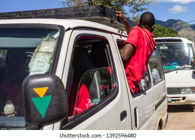 """Manica / Mozambique - May 01 2019: Bus conductor also known as """"cobrador"""" in Mozambique calling passengers through the window of mini bus taxi locally known as """"chapa"""""""