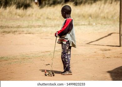 Manica, Mozambique - September 08, 2019: Boy playing with artesanal sticks and wire toy car