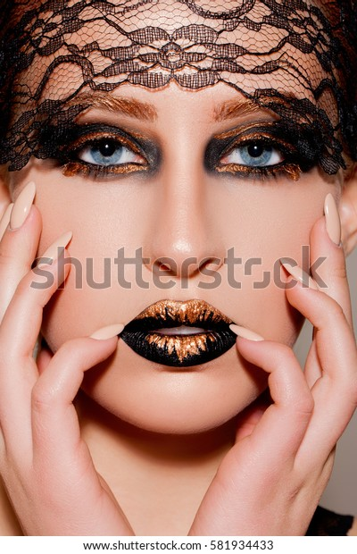Manicure. Beautiful Young Woman with Extravagant make-up. Close up Portrait. Fashion Model Girl Face. Professional Makeup. Fashion shiny highlighter on skin. Perfect manicure. Extravagant make-up.