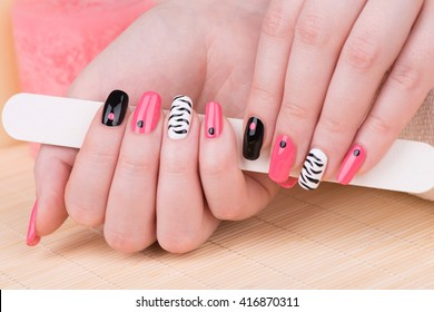 Manicure - Beautifully manicured woman fingernails. Feminine nail art with interesting animal print nail art. Selective focus.