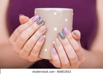 Manicure - Beauty photo of nice manicured woman fingernails holding a cup. Very nice feminine nail art with nice purple,silver and grayish nail polish. Processed in retro colors. Selective focus.