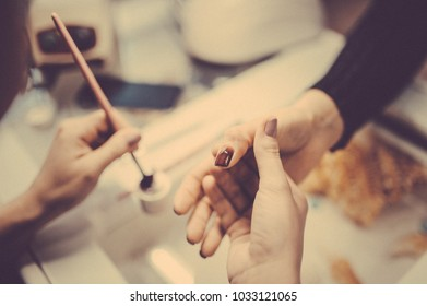 Manicure in beauty salon. Selective focus on brush. Toned image. Manicure process close up view