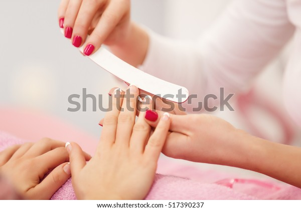 Manicure in beauty salon. Selective focus on costumer's nails.