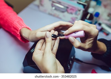 Manicure. Beauty saloon. Close-up.Apply black nail polish.