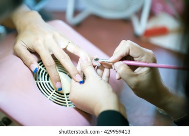 Manicure. Beauty saloon. Close-up.Apply  nail tone blur