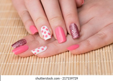 Manicure - Beauty treatment photo of nice manicured woman fingernails. Feminine nail art with nice glitter, pink and white nail polish. Selective focus.