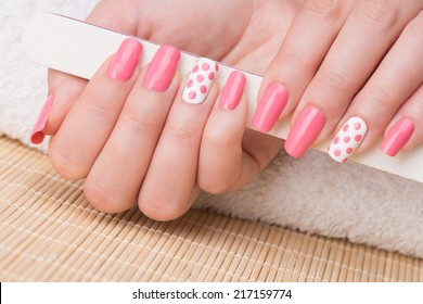 Manicure - Beauty treatment photo of nice manicured woman fingernails holding nail file. Feminine nail art with nice glitter, pink and white nail polish.
