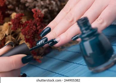 Manicure - Beauty treatment photo of nice manicured woman fingernails. Very nice  nail art with petroleum blue nail polish. Selective focus.