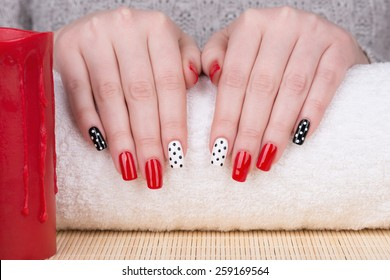 Manicure - Beauty treatment photo of nice manicured woman fingernails. Very nice feminine nail art with nice red, white and black nail polish.