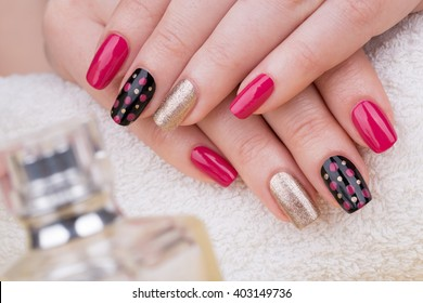 Manicure - Beauty treatment photo of nice manicured woman fingernails. Very nice feminine nail art with nice pink, gold and black nail polish.