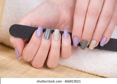 Manicure - Beauty treatment photo of nice manicured woman fingernails holding a nail file. Very nice feminine nail art with nice purple,silver and grayish nail polish. Selective focus.