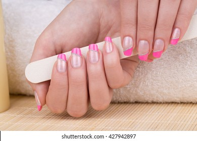 Manicure - Beauty treatment photo of nice manicured woman fingernails. Very nice pink French manicure with silver detail.