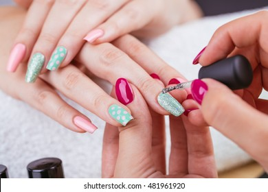 Manicure - Beauty treatment photo of nice manicured woman fingernails. Very nice feminine nail art with nice pink and light green nail polish. Polka dots design. Selective focus.
