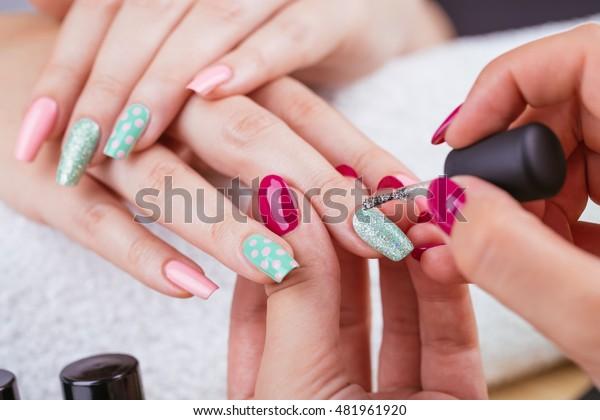 Manicure - Schönheitsbehandlungen Foto von hübschen, manikürten Fingernägeln. Sehr schöne feminine Nagelkunst mit schönem Rosa und hellgrünem Nagellack. Polka Dots Design.Selektiver Fokus.
