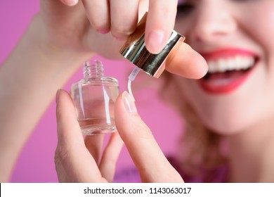 Manicure. Care of fingers of hands, nail varnish coating. Manicure process, beauty salon. Nail polish being applied to hand. Nail painting transparent nail polish. Treatment. Selective focus on bottle