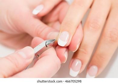 Manicure - cutting fingernail cuticles, close-up