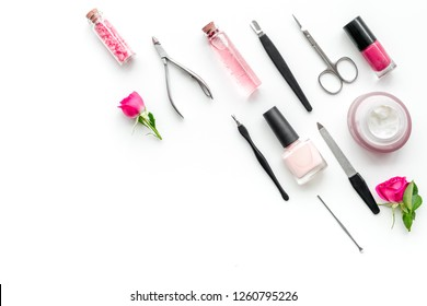 manicure equipment with nail polish and rose petals white background top view space for text