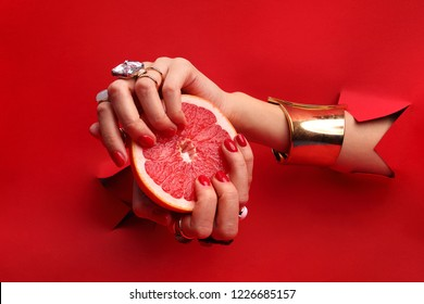Manicure. Female hands with red nails through a hole in a red background are holding a grapefruit fruit.
