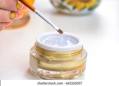 Manicure Gel nails. Master make nail extension. Gel nail transparent polish jar bottle closeup