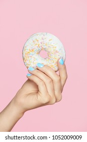 Manicure. Hand With Blue Nails Holding Donut. Close Up Of Female With Beauty Blue Manicure Holding Sweet Donut In Hand On Pink Background. High Quality Image.