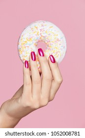 Manicure. Hand With Pink Nails Holding Donut. Close Up Of Female With Beauty Pink Manicure Holding Sweet Donut In Hand On Pink Background. High Quality Image.
