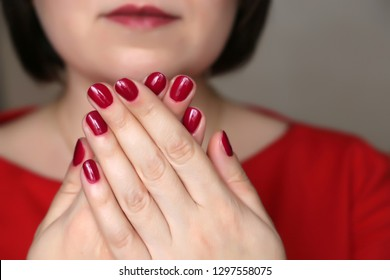Manicure and makeup, female cosmetics. Perfect hands with red nail polish, part of  face with red lips of middle aged woman