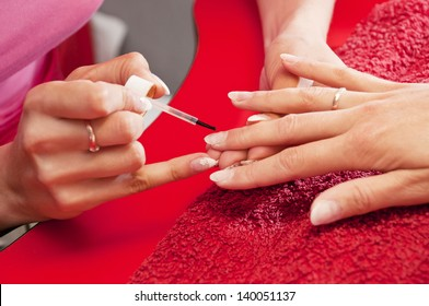 Manicure making on young women's hand. Focus on brush and polish on the fingernail.