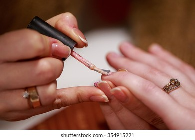 a manicure master is covering nails of her client with a nail polish