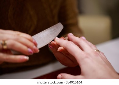 a manicure master is filing nails of her client