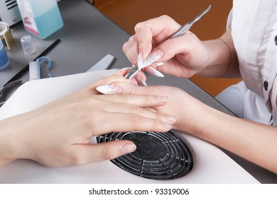 Manicure. Moving aside cuticle from the surface of the nail