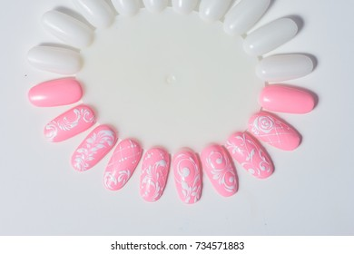Manicure nail color design samples pink rose flowers. Nail art handmade samples on a white background. Design templates for beauty salon. Selective focus. Close up