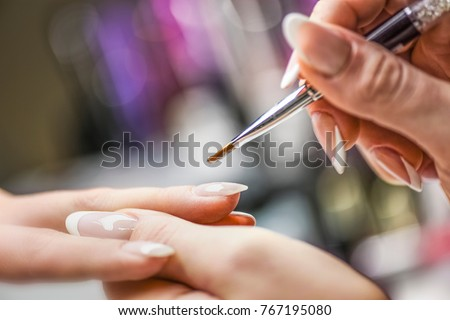 Manicure nail paint with thin brush on colour background,Nails artist polish, modelation gel