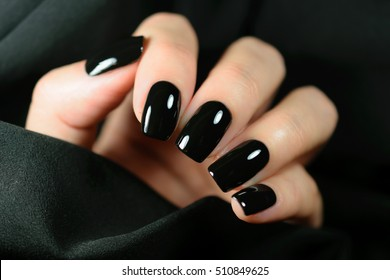 Manicure on female hands with black nail polish