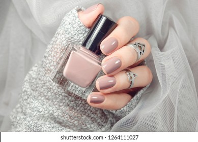 Manicure on female hands with nude nail polish on the grey background.