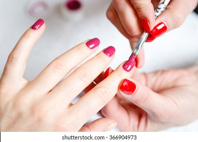 Manicure in process - Beautiful manicured woman's nails with red nail polish. The industry of beauty and nail care, beauty salons, soft focus
